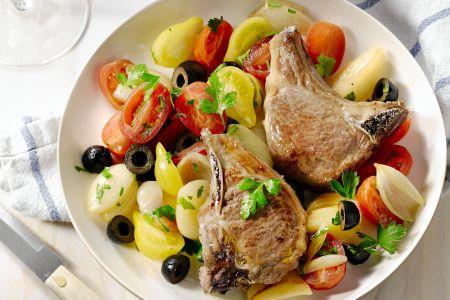Lamskoteletjes met warme salade van sjalot, olijven en tomaat