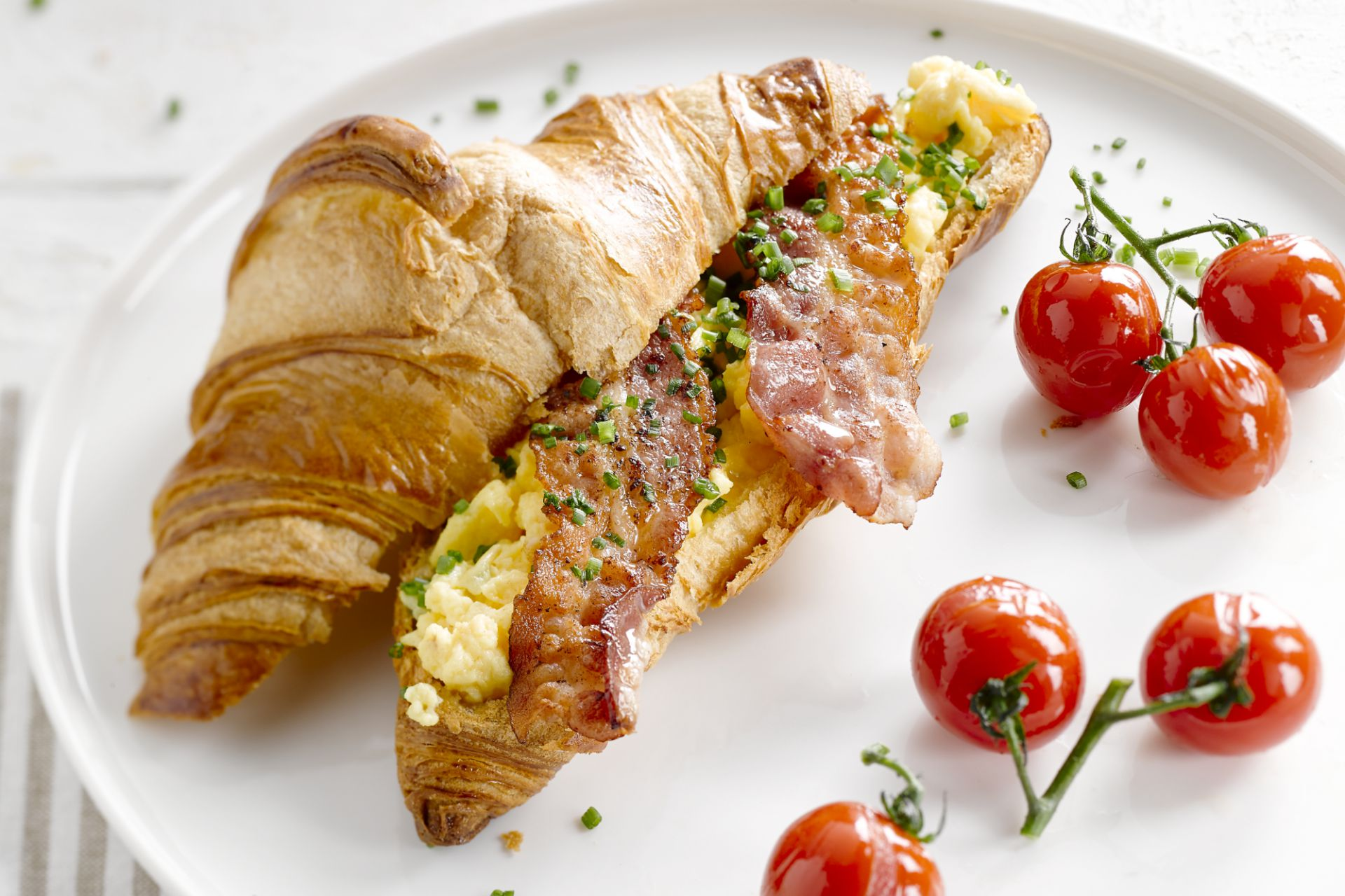 Croissant met roerei, ontbijtspek en geroosterde tomaten