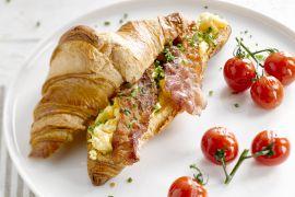 Foto van Croissant met roerei, ontbijtspek en geroosterde tomaten