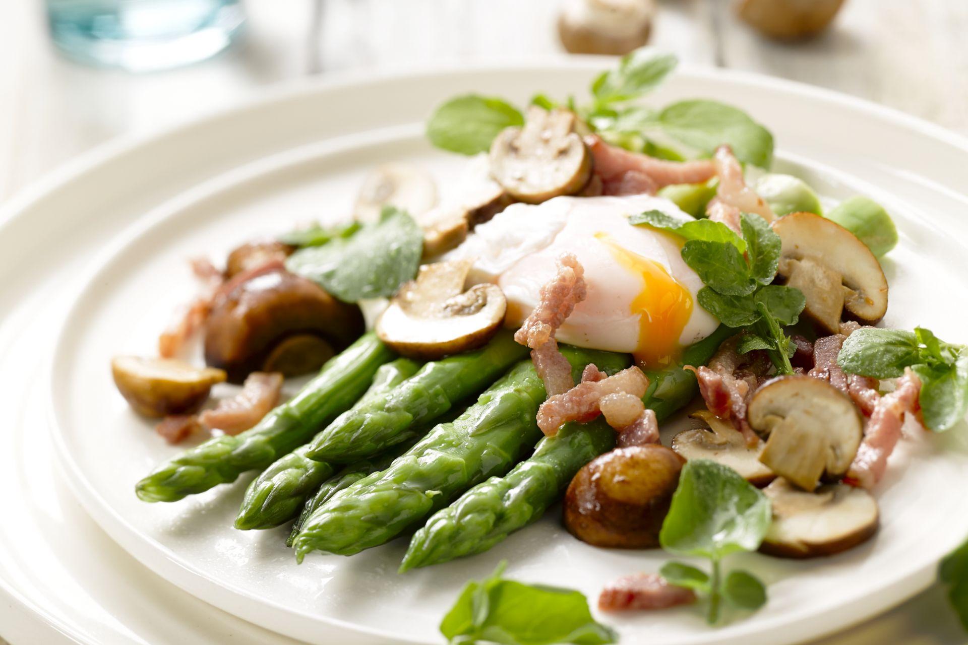 Salade van asperges met een gepocheerd eitje, champignons en rucola