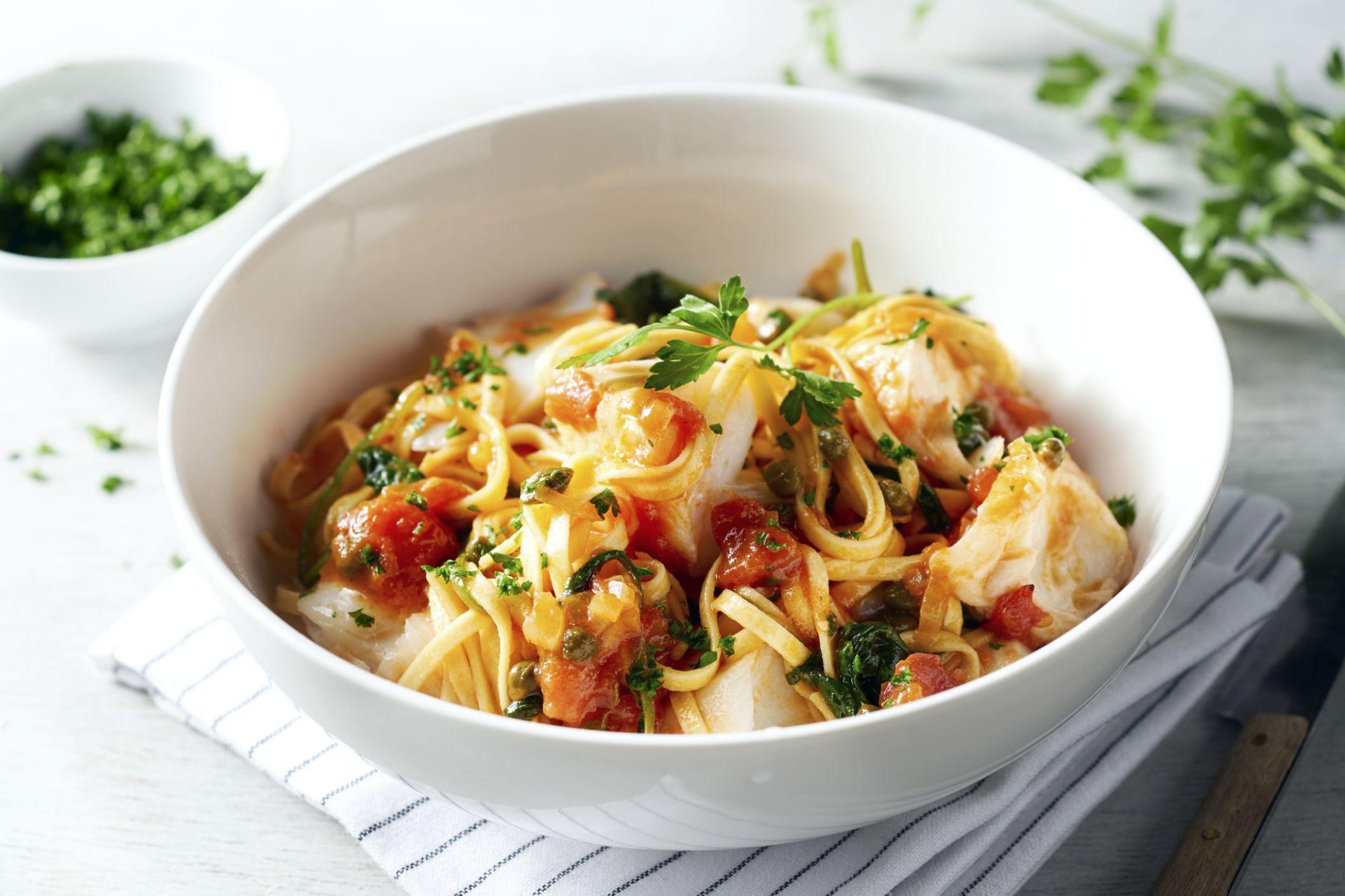 Linguine met kabeljauw in een mediterraanse tomatensaus