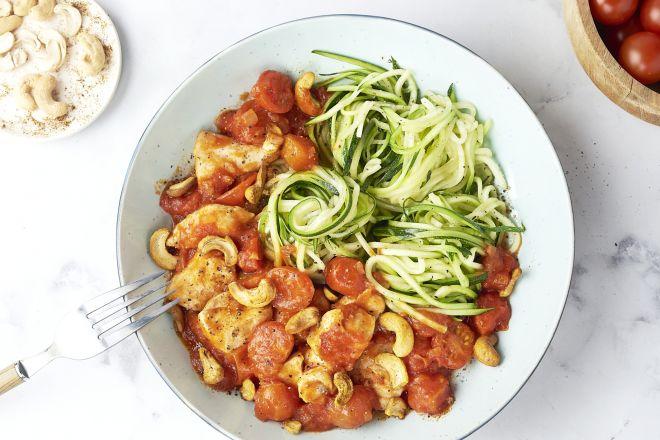 Courgettespaghetti met kip in tomatensaus en kruidige cashewnoten