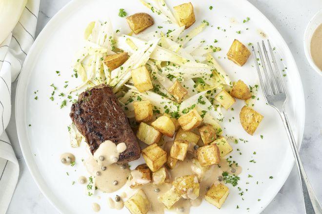 Steak met peperroomsaus, witloofsalade en geroosterde aardappelen