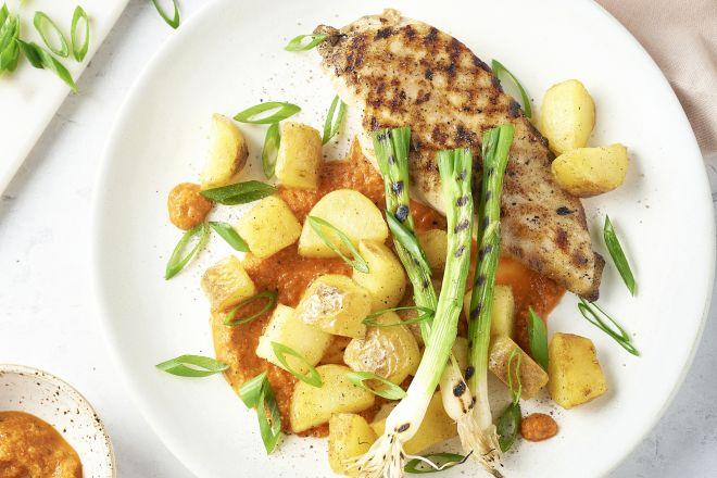 Gegrilde kip en lente-ui met romescosaus en gebakken aardappelen