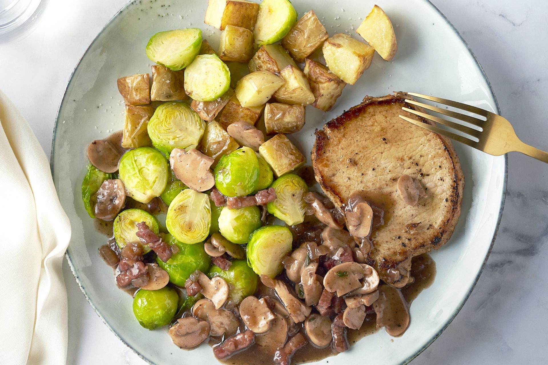 Varkenslapje met jagersaus, geroosterde spruitjes en aardappelen