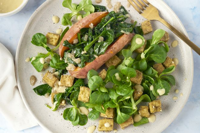 Gepofte zoete aardappel met krokante tofu, spinazie en citroen-tahin dressing