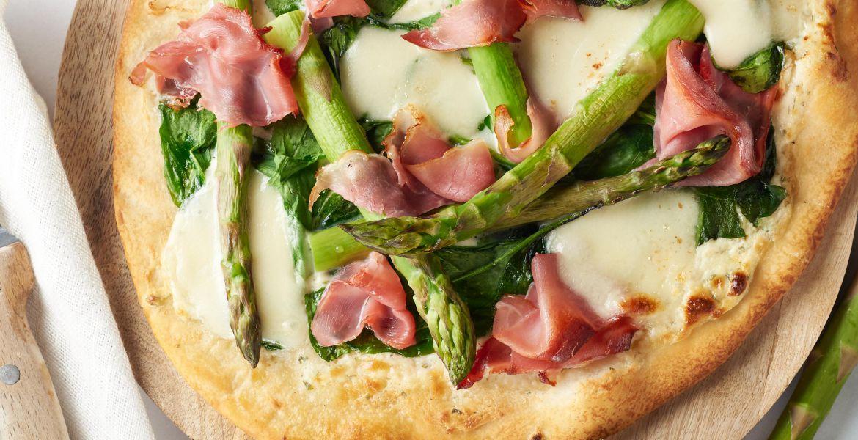 Witte pizza met groene asperges en gerookte ham